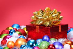 Christmas Gift with Gold Bow and Colorful Balls over red Royalty Free Stock Image