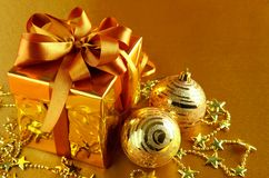 Christmas gift in gold box with bow stock photography