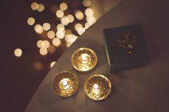 Christmas gift and golden candles Stock Photos