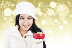 Christmas gift on golden lights background. Woman with white winter clothes is giving you a red christmas gift on golden defocused lights background Stock Photo