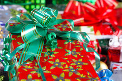 Christmas gift with a green ribbon. Wrapped Christmas gift with a green ribbon with golden stripes.  The wrapping paper has yellow flowers on a red background Royalty Free Stock Photography