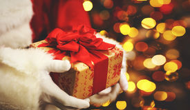 Christmas gift in hand Santa Claus Royalty Free Stock Image