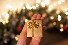 Christmas gift or Happy New Year.A small golden gift box. A gift for Christmas and New Year. packaging for jewelry royalty free stock photography