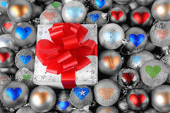Christmas gift and heart baubles Royalty Free Stock Image
