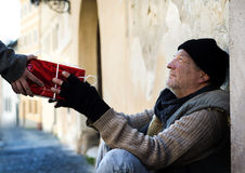 Christmas gift for homeless man. A girl's hand is giving a christmas gift to homeless man stock image
