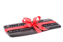 Christmas gift - keyboard. Christmas gift - computer keyboard with red ribbon royalty free stock photos
