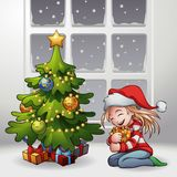 A Christmas Gift. A little girl sitting on the floor hugging her lovely gift Stock Images