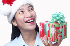 Christmas Gift For Me. Happy beautiful lady with christmas gift looking upward. Isolated in white background Stock Images