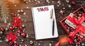 A Christmas gift, money packed with red slack, Xmas items, on a wooden background. Top view. Text space in the notebook. Effect of light and snowflakes stock photography