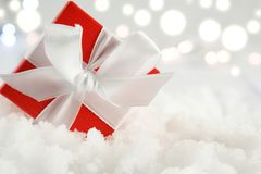 Christmas gift nestled in snow. Christmas gift with white bow nestled in snow on a bokeh lights background Stock Photos