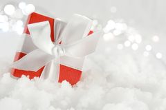 Christmas gift nestled in snow. Red Christmas gift with white silk bow nestled in snow Royalty Free Stock Image