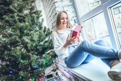 Beautiful girl sitting near New Year tree with gift royalty free stock photography