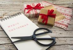 Christmas gift, notebook, scissor on wooden backg Stock Photo