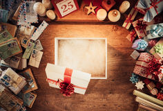 Christmas gift. Open empty Christmas gift box on a wooden desktop surrounded by letters and presents, top view stock photography