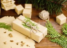 Christmas gift in organic craft paper and tree branches with twi Royalty Free Stock Photography