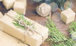 Christmas gift in organic craft paper and tree branches with twi Royalty Free Stock Photo