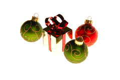 Christmas gift and ornaments. Christmas shiny gift box and tree ornaments isolated on white background with a red ribbon Royalty Free Stock Image