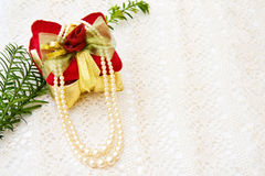 Christmas gift and pearls on old lace. Celebrating Christmas with gift decoration and vintage pearls sitting on old, handmade lace royalty free stock photo