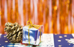 Christmas gift and pine cone decoration. A small christmas gift and a small pine cone with sparkling background Royalty Free Stock Images