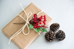 Christmas gift  and pine cones on a silver background Royalty Free Stock Images