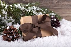 Christmas Gift With Pne Cones and Tree Branch on Snowy Surface stock photo