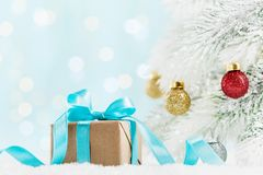 Christmas gift or present box and fir tree with balls decorations against turquoise bokeh background. Holiday greeting card. stock image