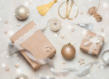 Christmas gift or present box wrapped in kraft paper with decoration on rustic background from above. Flat lay style. Top view. Bright and festive Royalty Free Stock Images