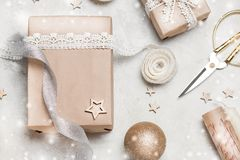 Christmas gift or present box wrapped in kraft paper with decoration on rustic background from above. Flat lay style. Top view. Bright and festive Stock Photography