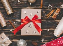 Christmas gift or present box wrapped in kraft paper with decoration on rustic background from above. Flat lay style. Top view. Bright and festive Royalty Free Stock Photography