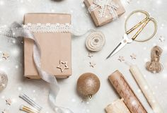 Christmas gift or present box wrapped in kraft paper with decoration on rustic background from above. Flat lay style. top view. Br. Ight and festive Stock Images