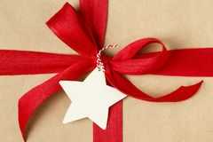 Christmas gift present decorated with bright red bow and blank gift tag. Simple, recycled kraft wrapping paper background. Close-up of festive Christmas gift royalty free stock image