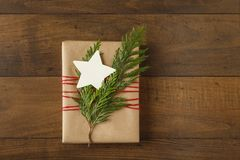 Christmas gift present with recycled wrapping paper and natural evergreen decorations on wood background