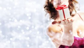 Christmas gift present, woman with package on blurred bright lig. Hts background, banner template with copy space stock images