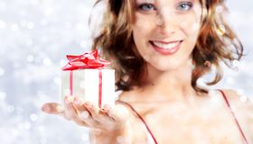 christmas gift present, woman with package on blurred bright lig stock photography