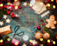 Christmas gift and presents wrapping with holiday cookies and handmade paper boxes on dark vintage background with festive bokeh l Stock Photos