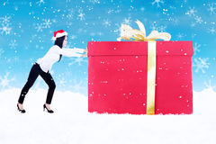 Christmas gift pushed by woman on blue background Stock Photo