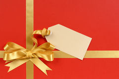 Christmas gift red background, gold ribbon bow, gift tag, copy space Stock Image