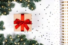 Christmas gift with red bow. Fir branches, stars and paper for packaging. Flat lay style Stock Image