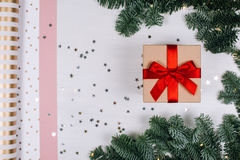 Christmas gift with red bow. Fir branches, stars and paper for packaging. Flat lay style Royalty Free Stock Image