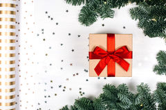 Christmas gift with red bow. Fir branches, stars and paper for packaging. Flat lay style Royalty Free Stock Images