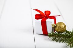 Christmas gift with red bow, spruce branch and balls. Beautiful still life on a wooden table Stock Photography
