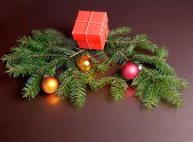 Christmas gift red box, colored balls and christmas tree on dark mirror table. Celebrities composition. Selective focus. Christmas gift red box, colored balls Royalty Free Stock Images