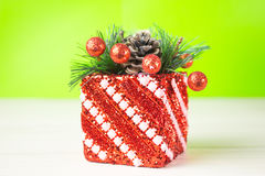 Christmas gift in red box on a green and white background the table. Decoration of fir branches beads. stock photos