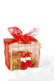 Christmas gift in red and gold in the snow. Royalty Free Stock Images