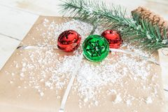 Christmas gift with red and green jingle bells. Brown wrapped christmas gift with red and green jingle bells and a tree sprig with a pinecone Royalty Free Stock Photo