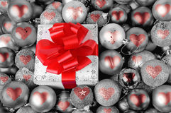 Christmas gift and red heart baubles Stock Photography