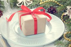 Christmas gift with red ribbon on cyan plate with fir-tree branches on white wooden table. Xmas table setting with gift box close up Royalty Free Stock Photo