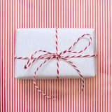 Christmas gift with red ribbon on stripes surface. Top view. Square. Christmas gift with red ribbon on stripes surface. Top view. Square image Royalty Free Stock Image
