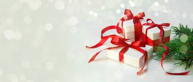 Christmas Gift`s in white box with red ribbon on light background. New year holiday composition banner. Copy space Royalty Free Stock Images
