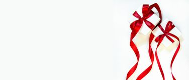 Christmas gift`s in white box with red ribbon on light background. New year holiday composition banner. Copy space for your text Royalty Free Stock Photo